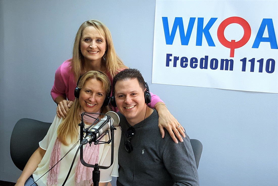 Dr. Christine Bacon and her brightly smiling, newly engaged guests Dr. Joy Francis and Michael Corley in the WKQA studio.