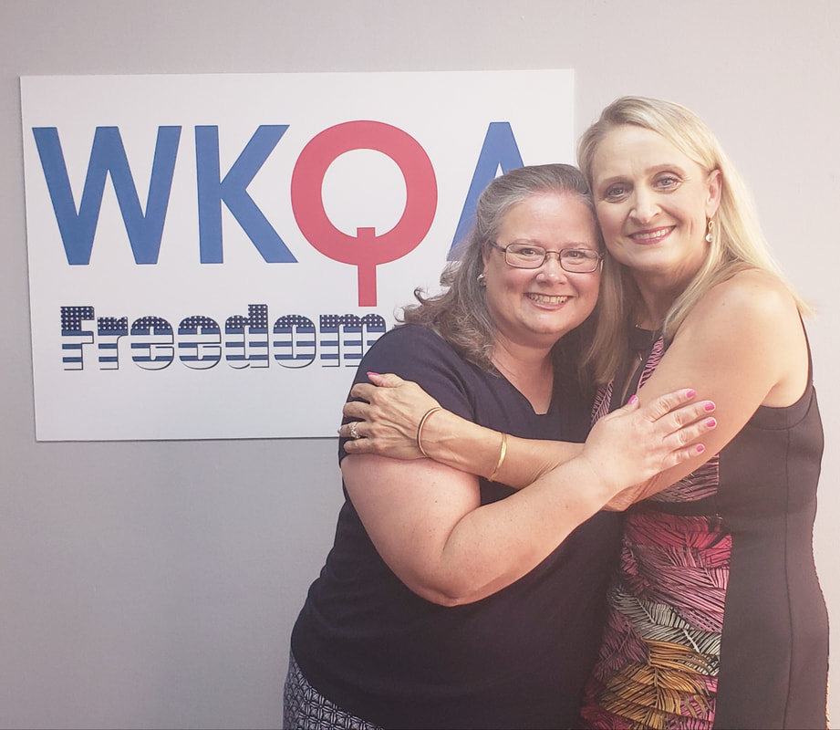Christine Tate and Christine Bacon hug underneath the WKQA sign in the Norfolk studios.
