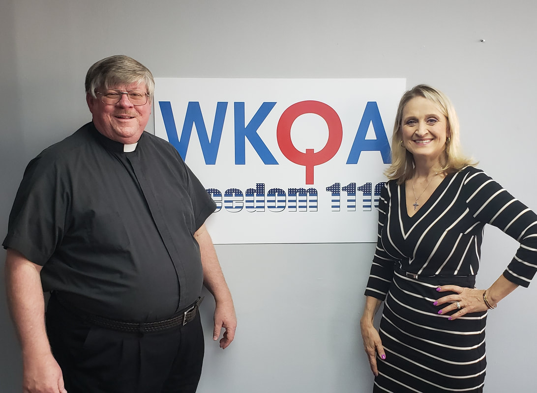 Dr. Christine Bacon and Deacon Darrell Wentworth standing near the WKQA sign in the studio.