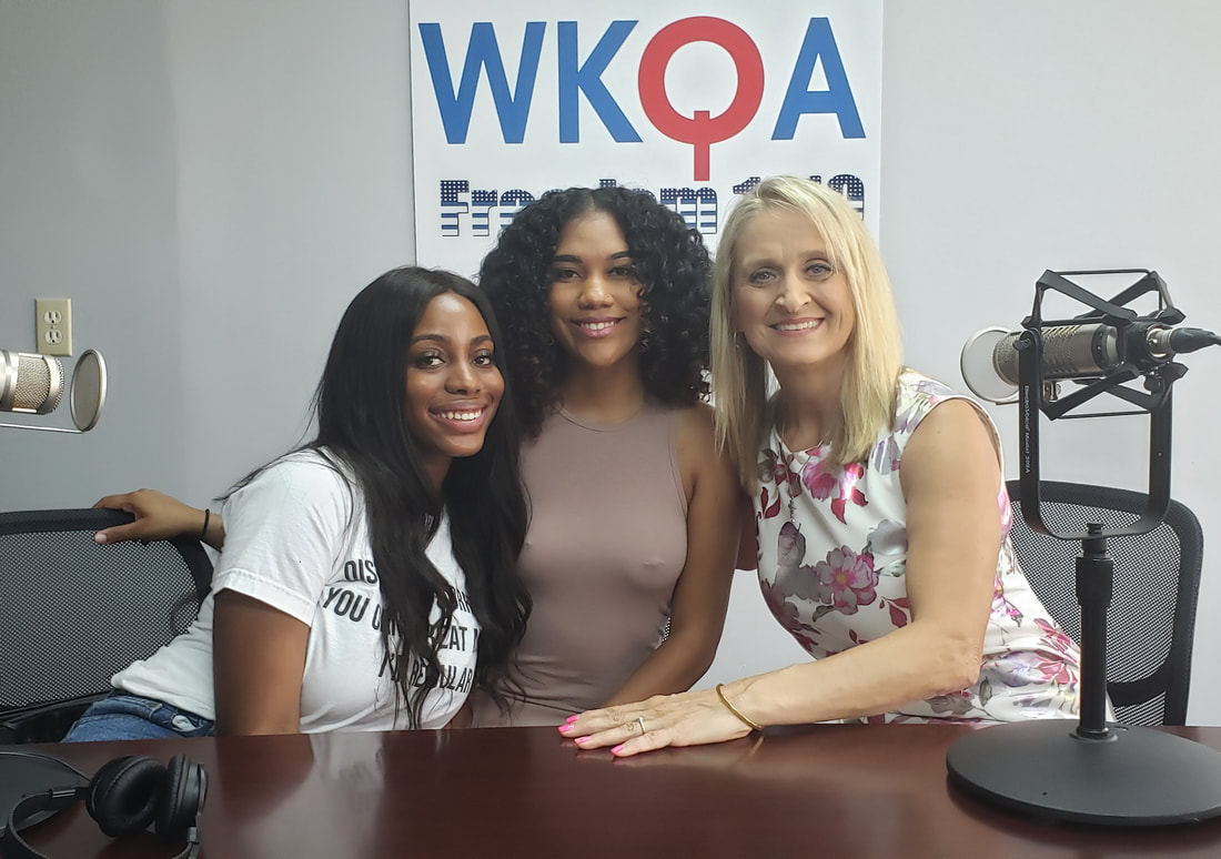 Jazmyn, Nykki and Dr. Bacon sit together and share a hug behind the WKQA radio desk.