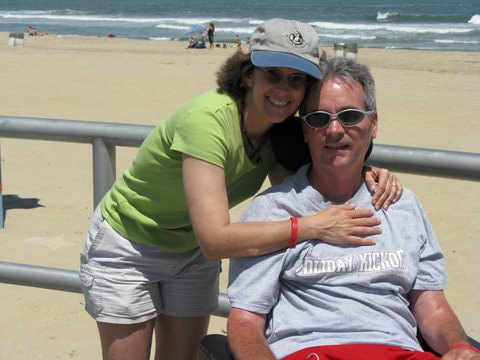 The smiling AJ has her arms wrpped around her always joful husband Jeff, already in a wheelchair, outside in front of the oceanfront with the sun at their backs.