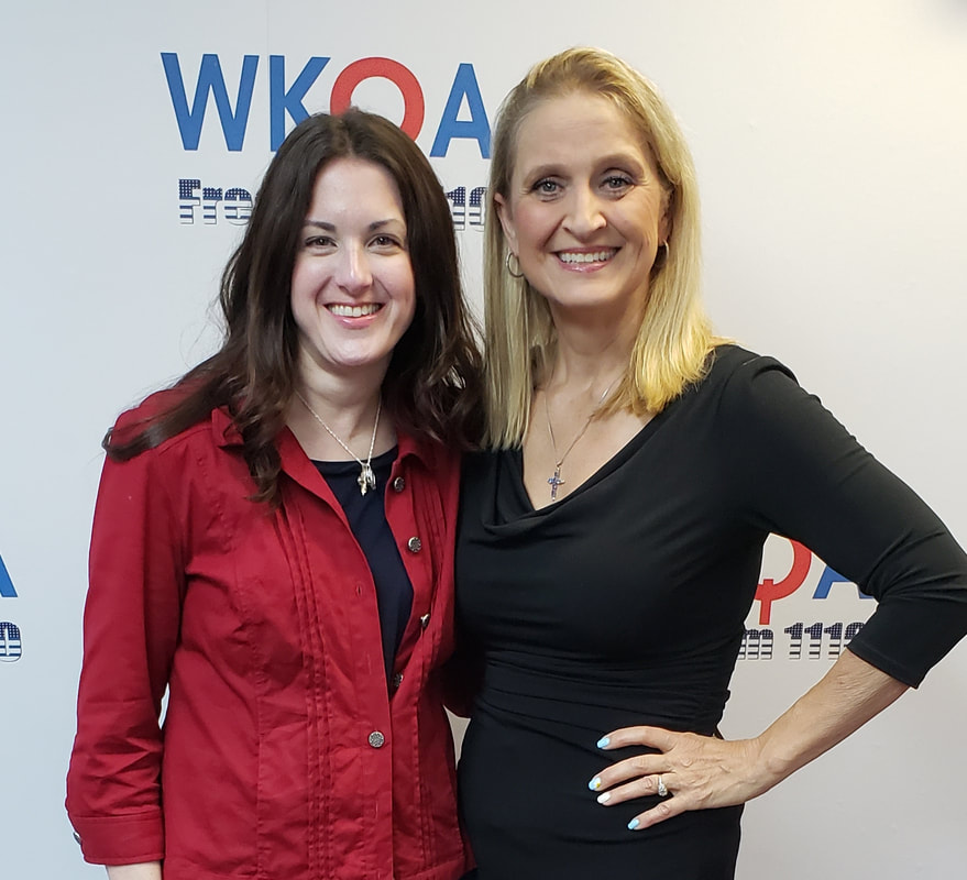 Dr. Christine bacon and her guest pose in front of the WKQA sign in the Hampton Roads studio.