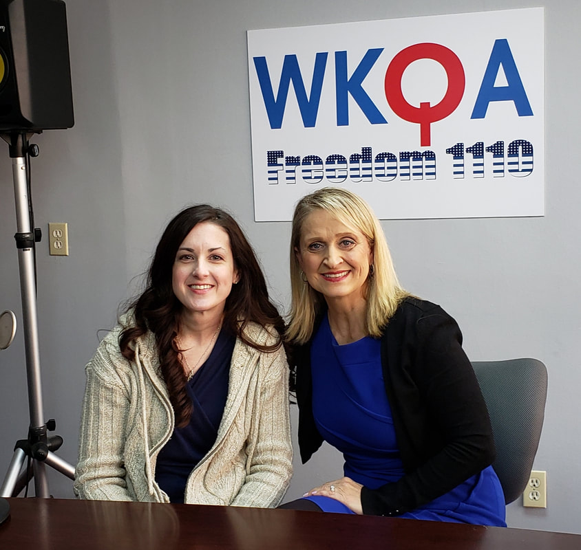 Dr. Christine Bacon and Jenifer Hartline sitting behind the broadcast desk in the WKQAstudios.
