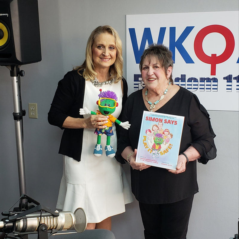 Dr. Christine Bacon in the WKQA studios holding the green and purple Simon doll while Regina, standing at her side, proudly displays her book