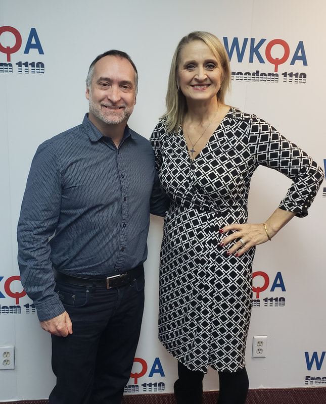 Dr. Christine Bacon and Scott Gilbert stand against the WKQA wall after another great broadcast.