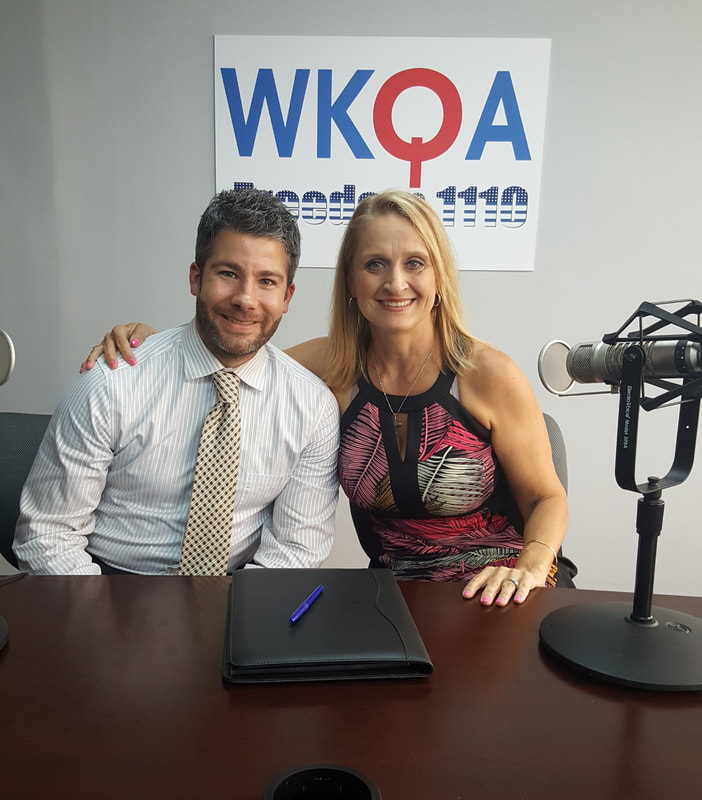 Dr. Bacon and guest Seth Doherty smile behind the WKQA radio desk.