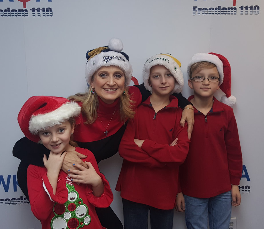 Dr. Bacon with three of her grandchildren hugging inside the WKQA studios.