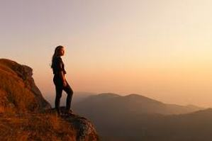Image of woman standing atop a mountain looking into the sunset.